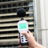 Sound level meter measuring the noise of industrial ventilation unit.